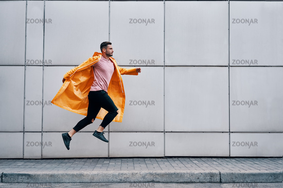 Trendy young man in yellow raincoat jumping in the air on wall street urban background