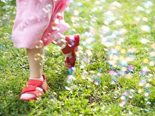Little Girl Running Through Soap Bubbles
