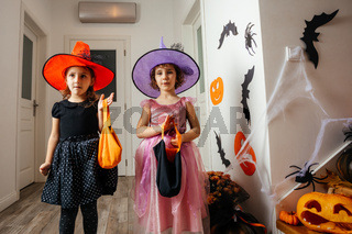 Little girls witches waiting for halloween treats