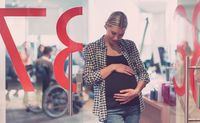 Portrait of pregnant businesswoman gently holding belly in modern office