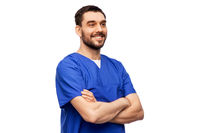 happy smiling doctor or male nurse in blue uniform