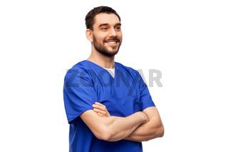happy smiling doctor or male nurse in blue uniform
