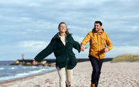couple running along autumn beach