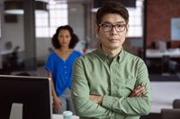 Portrait of serious asian businessman standing in office with female colleague in background