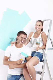 Laughing couple with a brush or roller for painting walls