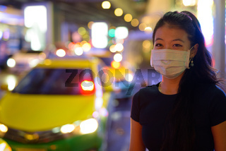 Asian woman wearing face mask to protect from covid 19 outdoors at night while at taxi station