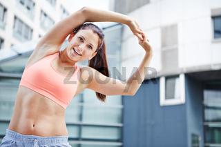 Sportliche Frau macht Dehnübung