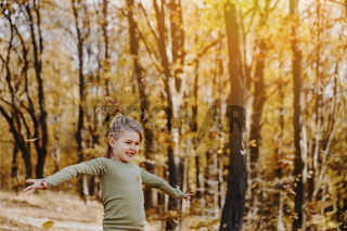 Small little girl is playing with yellow leaves in autumn forest or garden