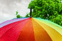 Rain On Rainbow Umbrella. Umbrella under heavy rain against cloudy sky background. Rainy weather