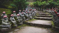 Buddha statues with knitted hat offerings along shrine path at the temple Diasho-in in Miyajima, Hiroshima, Japan