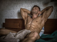 Totally naked sexy man with muscular body on bed