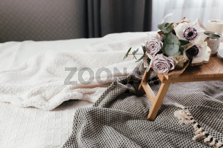 Coffee table on bed. Flowers, coffee cup and candles. Interior gray tones, plaid