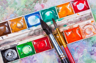 watercolor set and brushes on oil picture background