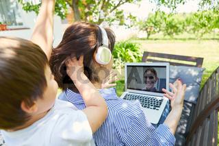 Alleinerziehende Mutter bei Videokonferenz mit Kind