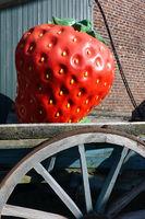 überdimensionale Erdbeere auf einem Holzkarren