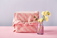 Flower of yellow matthiola with gift wrap in traditional japanese furoshiki style. Design concept of holiday greeting with carnation bouquet on pink table