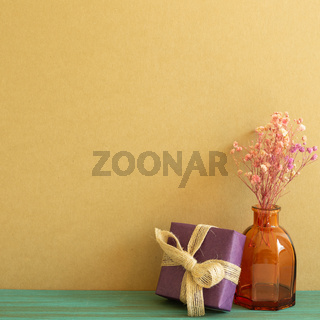 Purple gift box and dry flowers on wooden table. khaki brown wall background. copy space