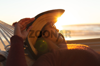 Mixed race woman on beach holiday lying in hammock relaxing during sunset