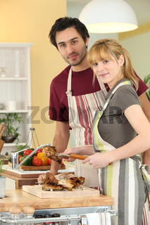 Young man and young woman cutting chicken