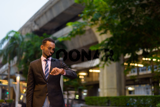 Portrait of handsome young African businessman outdoors in city at night checking wristwatch