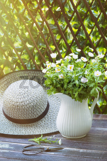 Sunhat with daisies in jug on table