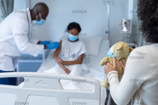 Mixed race woman holding teddy in hospital doctor in face mask giving covid vaccine to sick daughter