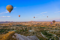 Cappadocia, Turkey - August 31, 2011: Hot air balloon flying over rocky landscape at sunrise in Cappadocia