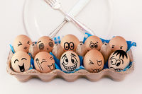 Easter eggs with different faces in eggbox and round plate with cutlery, knife and fork.