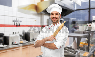 happy male chef with rolling pin at kitchen