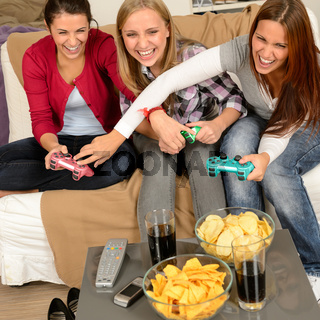 Laughing teenage girls playing with video game