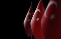 Small national flags of the Turkey on a black background