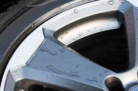 Detailaufnahme von modernen Autoreifen mit Alufelge und Wassertropfen