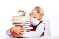 Young boy with protection mask against corona virus at school.
