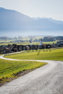 Path to Austrian mountain village with foggy valley background during fall in Wildermieming, Tirol, Austria