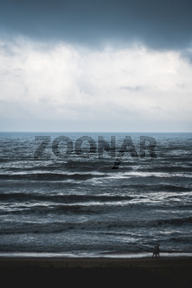 Couple walking on beach along stormy dark silver shining ocean in Daimus, Spain