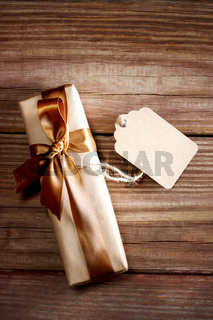 Gift box on a rustic wooden table with a blank tag