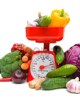 Kitchen scales and fresh ripe vegetables on white background