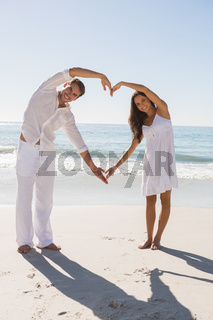 Romantic couple forming heart shape with arms