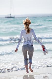 junge hübsche frau spaziert am strand im sand im freien im Sommer