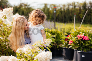 Mom and cute girl choose the plants for their garden