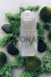 Bottle of water amidst moss and stones