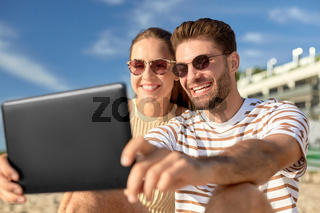happy couple with tablet pc at on summer beach