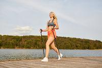 Junge Frau trainiert Fitness mit Nordic Walking
