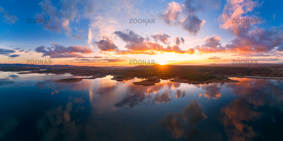 Drone aerial panorama of a lake reservoir of a dam with perfect reflection on the water of the sunset in Sabugal, Portugal