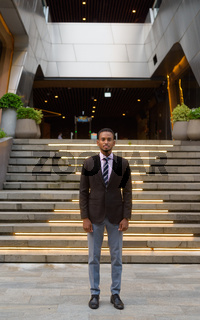 Full length portrait of handsome young African businessman outdoors in city