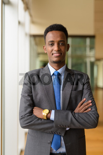 Portrait of handsome African businessman wearing suit and tie with arms crossed vertical shot
