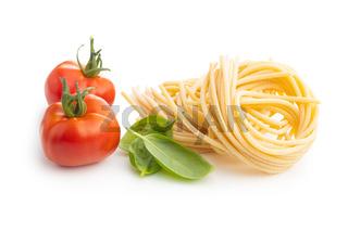 Italian pasta nest, tomato and basil leaves. Uncooked spaghetti nest
