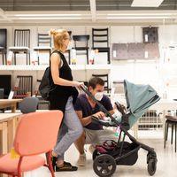 Young couple with newborn in stroller shopping at retail furniture and home accessories store wearing protective medical face mask to prevent spreading of corona virus when shops reopen