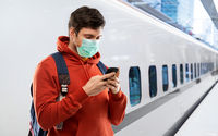 man in mask with smartphone traveling by train