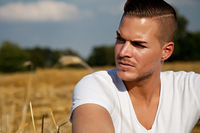 Portrait of  a beautiful young man outdoors in white casual shirt sitting on hay field